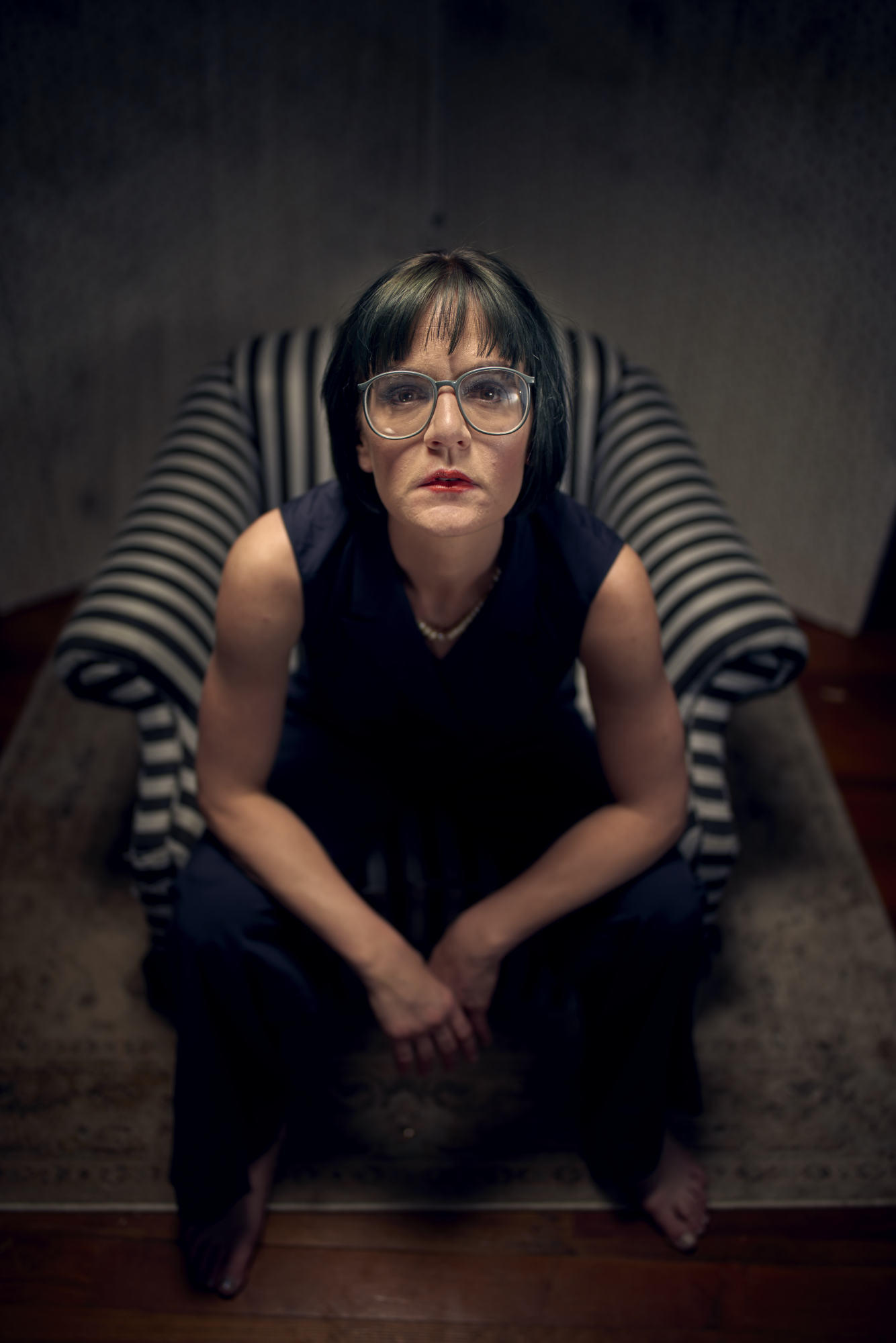 Editorial portrait of woman in grungy setting with glasses on.