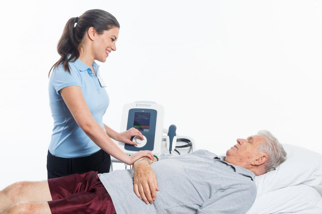Lifestyle photo of a model nurse using a medical device on a model patient.