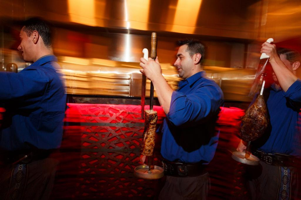 Texas De Brazil Waiters bringing steaks to the table during a Commercial Lifestyle Restaurant Photography Shoot