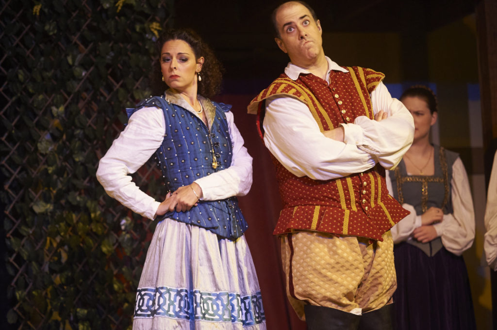 Beatrice and Benedick interact. Action on the stage during Much Ado About Nothing at the Curtain Theater in Austin, Texas.