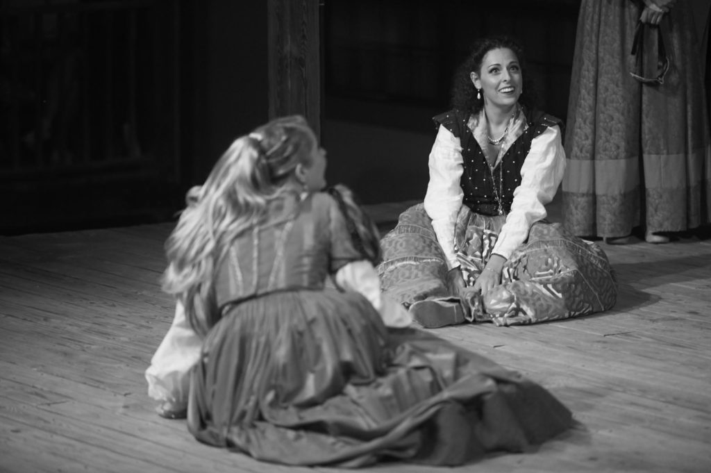 Hero and Beatrice sit on stage together. Action on the stage during Much Ado About Nothing at the Curtain Theater in Austin, Texas.