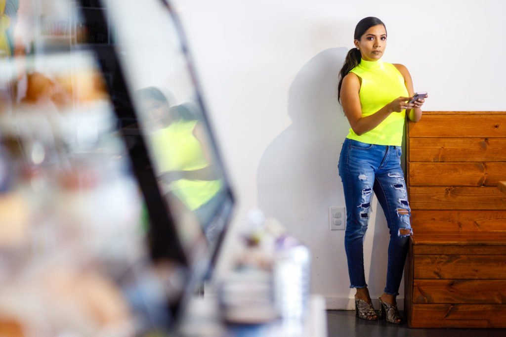 Haide wearing distressed jeans and a bright hello sleeveless turtleneck during her Personal Branding Session.
